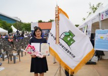 대리수상자 송주혜 사무국장이 표창장을  들고 기념사진 촬영을 하고 있다.